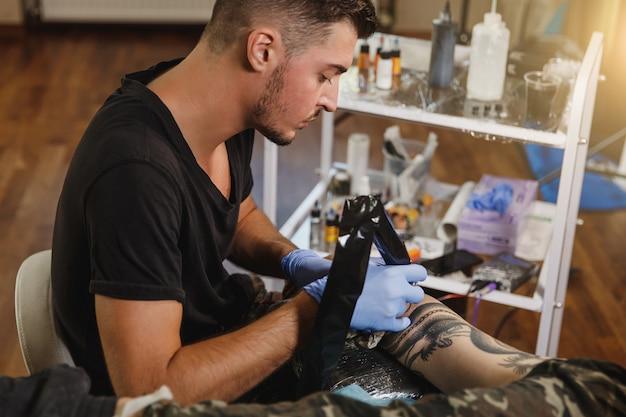 Un artiste tatoueur professionnel faisant un tatouage sur le bras d'un jeune homme par machine avec de l'encre noire