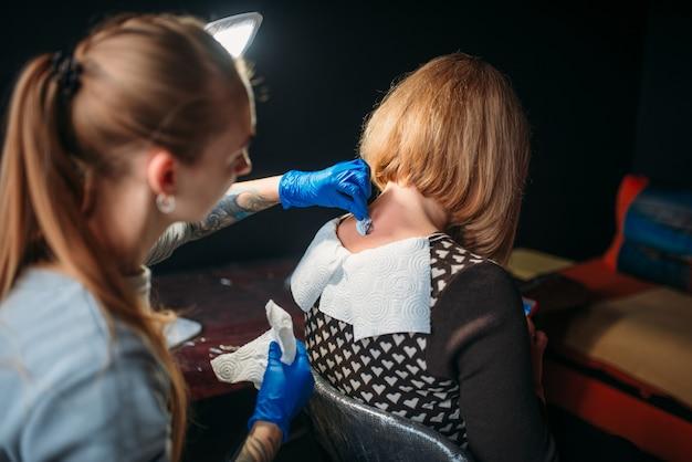 Une artiste tatoueuse en gants stériles bleus prépare la peau du client pour le tatouage. salon de tatouage