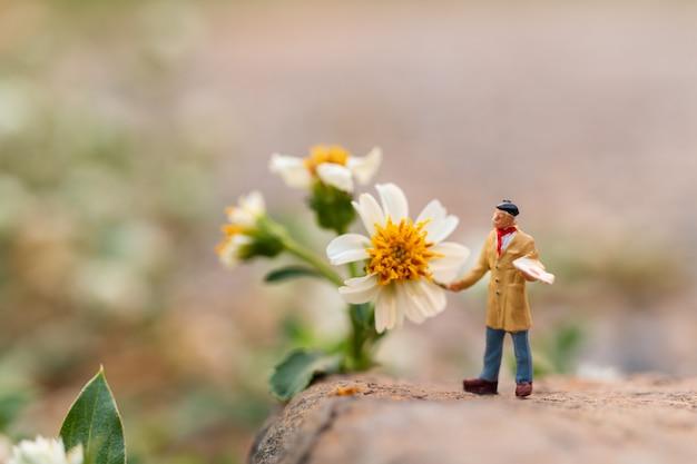 Artiste tenant un pinceau et peignant une fleur dans le jardin
