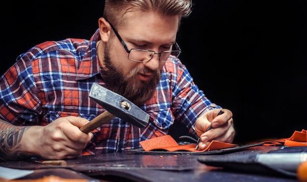 Artiste travaillant avec le cuir créant la maroquinerie dans l'atelier de tannerie
