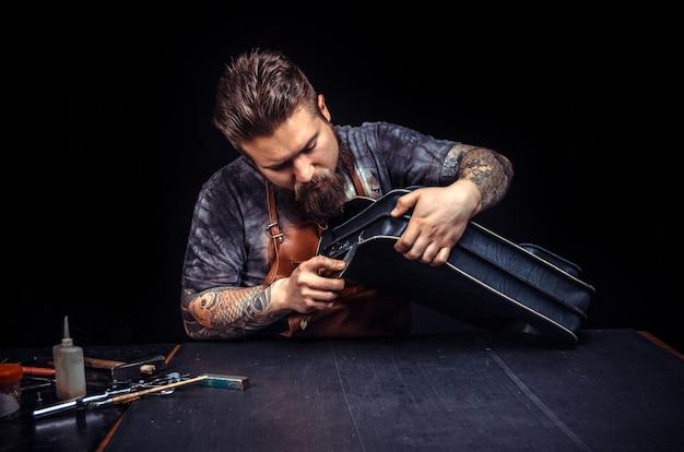 Artiste travaillant avec le cuir passionné par son entreprise dans son atelier de cuir.
