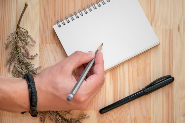Artiste travaillant sur un nouveau projet dans un cahier vide