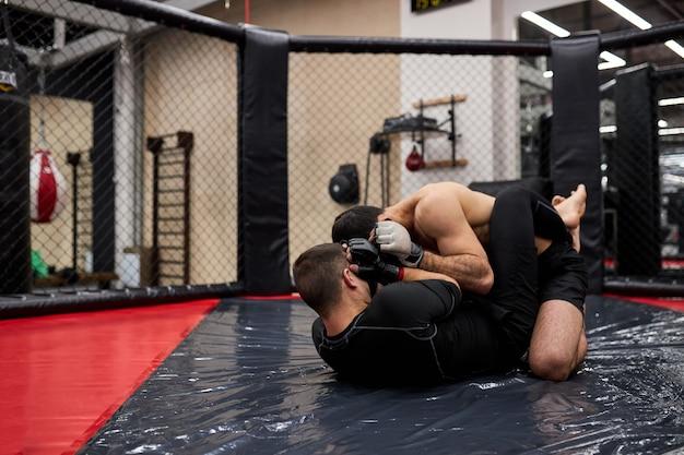 Artistes martiaux mixtes avant le combat, de jeunes combattants mma caucasiens se battent sur un anneau au sol se préparant à la compétition dans les arts martiaux