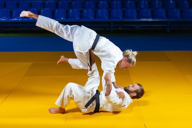 Arts martiaux. porteurs épargnants. sport homme et femme en kimono blanc train judo jette et capture dans la salle de sport
