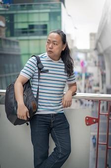 Asain / thaï-chinois aux cheveux noirs longs avec un t-shirt bleu réfléchit et tient son sac à dos sur son sholder près du train aérien.