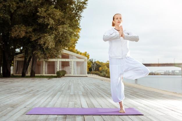 Asana compliqué. concentré jeune femme debout en position asana tout en faisant du yoga du matin