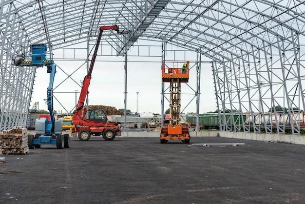 Ascenseur avec travail de plate-forme dans le champ de construction de hangar à entrepôt