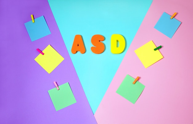 Asd, concept de l'autisme avec des autocollants en papier de couleur sur un fond multicolore