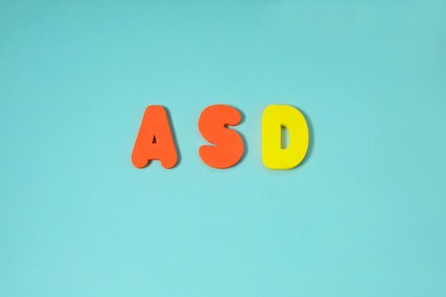 Asd, concept de l'autisme avec lettres de couleur sur fond bleu