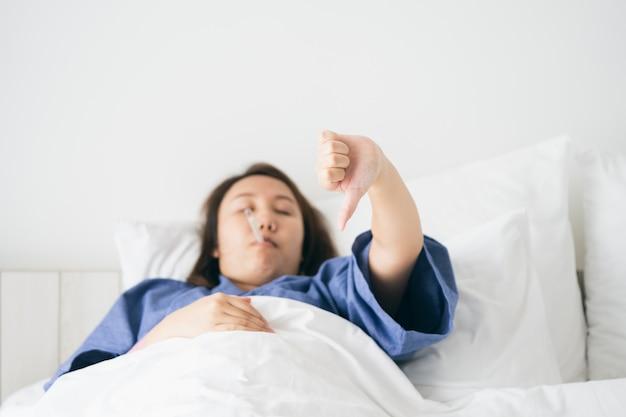 Asian beautiful woman l'hypothermie a été mesurée par la fièvre. s'allonger sur le lit