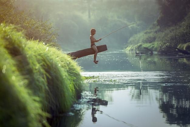 Asian boy pêchant à la rivière