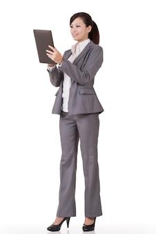 Asian business woman holding pad, portrait en pied sur fond blanc.