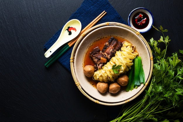 Asian food concept porc de nouilles aux œufs chinois et soupe de boulettes de viande sur fond noir avec espace de copie
