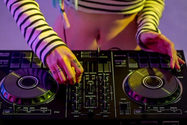 Asian girl dj joue sur une platine vinyle dans une soirée colorée.