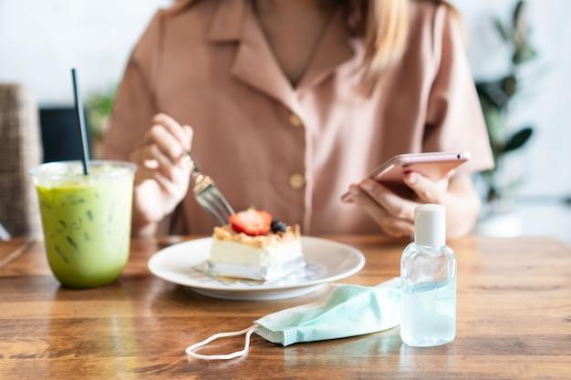 Asian girl eating cheese cake lors de l'utilisation de smartphone avec gel désinfectant et masque chirurgical sur table