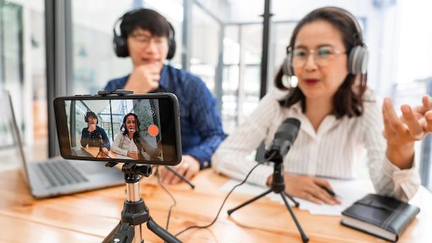 Asian man and woman podcasters dans des écouteurs enregistrant du contenu avec un collègue parlant au microphone et à la caméra en studio de diffusion ensemble, technologie de communication et concept de divertissement