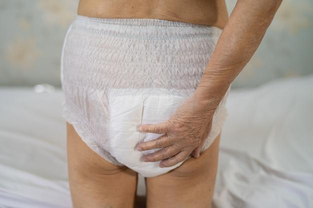 Asian senior woman patient portant des couches d'incontinence à l'hôpital de soins infirmiers