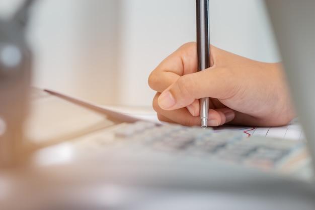 Asian student note sur un cahier tout en apprenant une étude en ligne ou un apprentissage par ordinateur portable