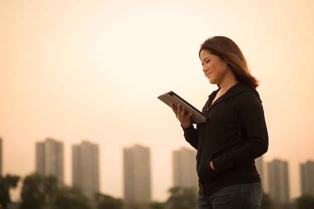 Asian woman holding tablet avec fond de ciel coucher de soleil