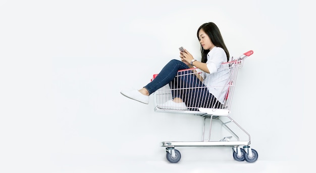 Asian woman shopping on mobile sitting in shopping cart