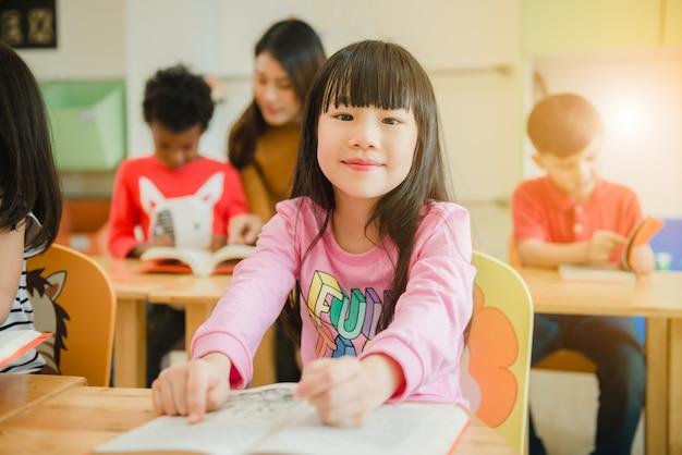 Asiat en lisant un livre en souriant à la caméra. rangée d'étudiants élémentaires multiethniques, lecture de livre dans la salle de classe à l'école. images de style effet vintage.