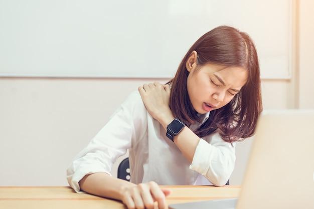 Asiat en robe décontractée blanche attraper cette épaule, en raison de la douleur du travail acharné.