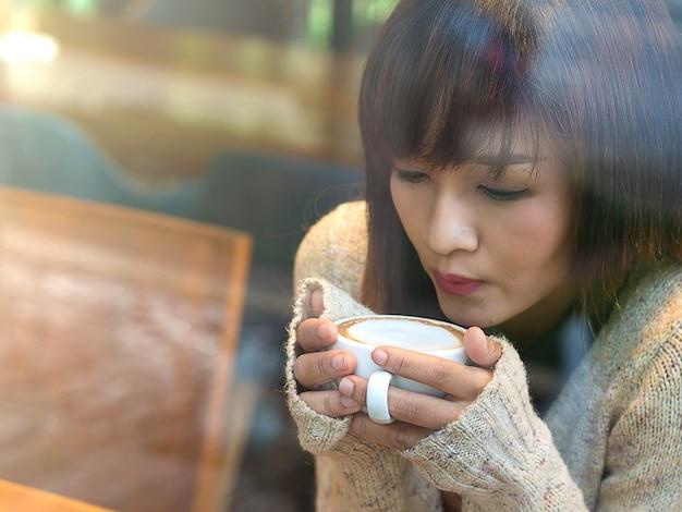 Asiat en sirotant un café chaud au café pour se détendre le dimanche matin