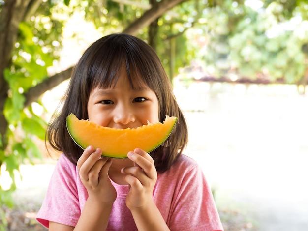 Asiat tenant tranche de melon orange sur les mains. on dirait que melon sourit.