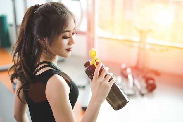 Asiatique belle femme buvant des protéines shake ou de l'eau potable dans la salle de sport sport fitness formation