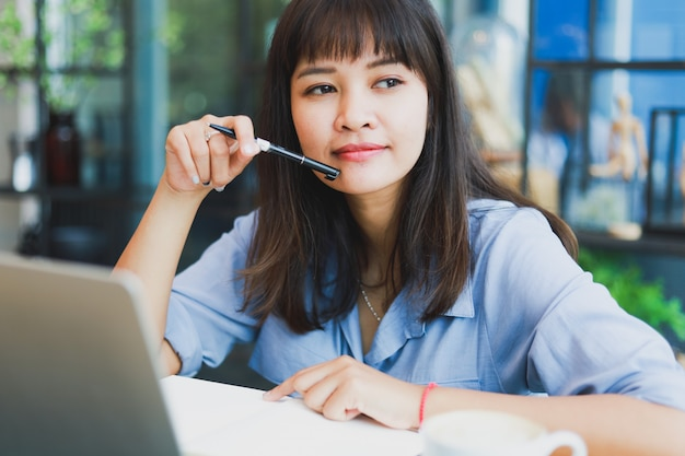 Asiatique belle femme en chemise bleue à l'aide d'ordinateur portable et de boire du café