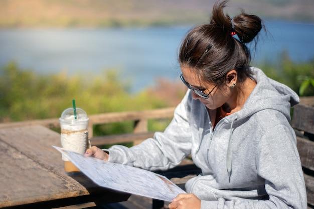 Asiatique belle femme lisant menu dans les mains au restaurant