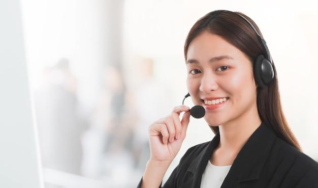 Asiatique belle femme souriante client assistance opérateur de téléphonie dans le bureau de fond.