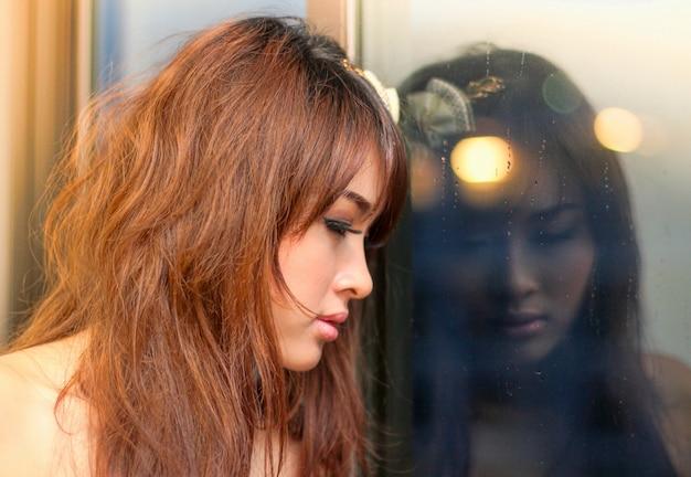 Asiatique belle jeune femme devant une fenêtre dans un jour de pluie et d'humeur solitaire.