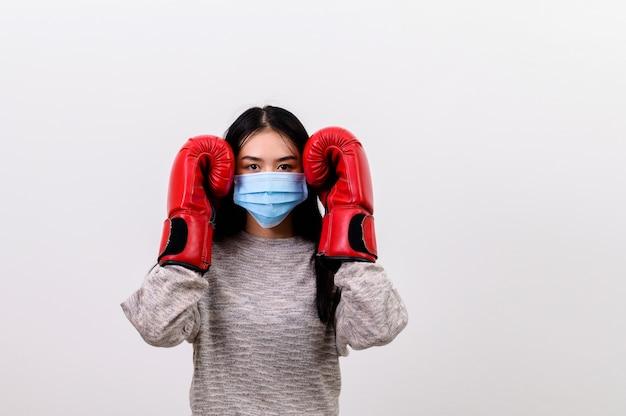 Asiatique belle jeune femme heureuse portant un masque de protection et des gants de boxe elle se prépare pour la lutte contre le coronavirus, avec copie espace