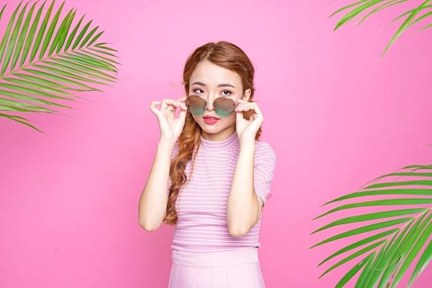 Asiatique belle jolie jeune fille attrayante dans le concept de l'été avec du jus d'orange et des feuilles de palmier