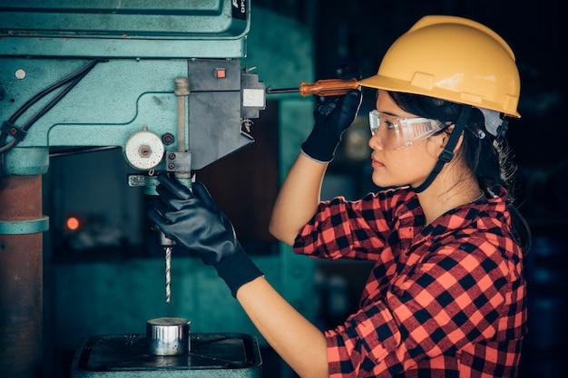 Asiatique beuatiful femme travaillant avec la machine dans l'ingénieur d'usine et le concept de femme travaillant ou jour de femme