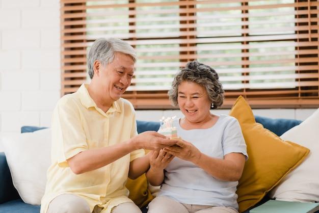 Asiatique couple de personnes âgées homme tenant gâteau célébrant l'anniversaire de sa femme dans le salon à la maison. un couple japonais profite d'un moment d'amour à la maison.