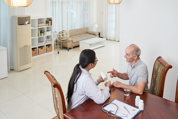 Asiatique, docteur, parler, à, vieux patient caucasien, chez soi, et, discuter, sur, médicament