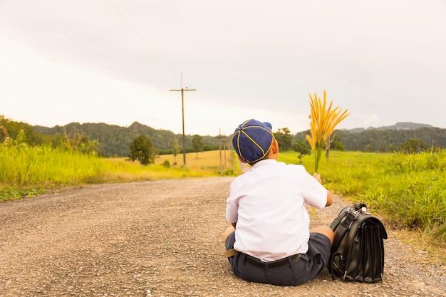 Asiatique étudiant assis et vue sur la campagne