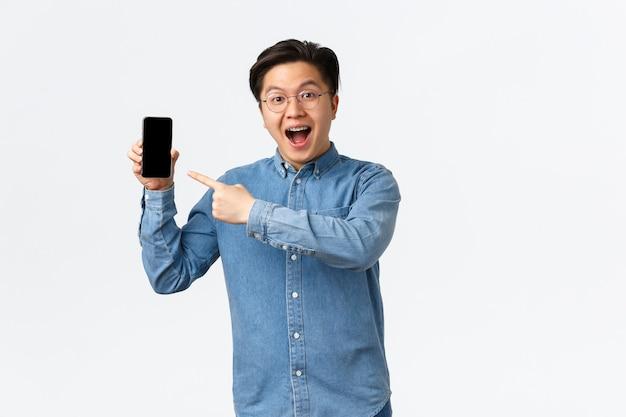 Un asiatique excité et impressionné portant des lunettes et des bretelles montrant une chose géniale sur l'écran du téléphone portable p ...