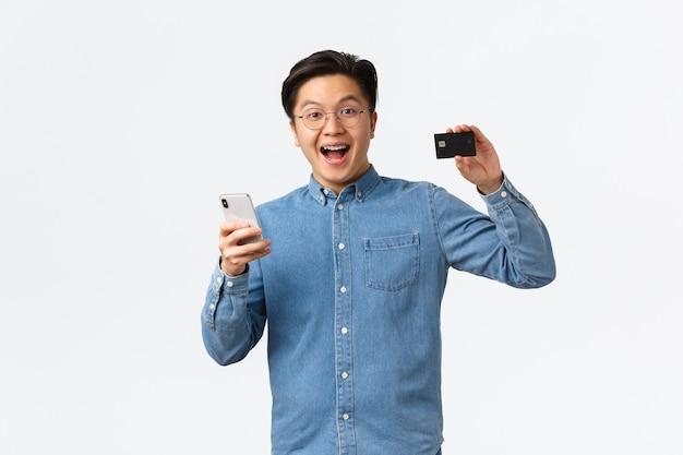 Un asiatique excité et satisfait dans des lunettes et des vêtements décontractés montrant une carte de crédit avec une expression fière, payant quelque chose sur internet à l'aide d'un smartphone, faisant des achats en ligne, fond blanc