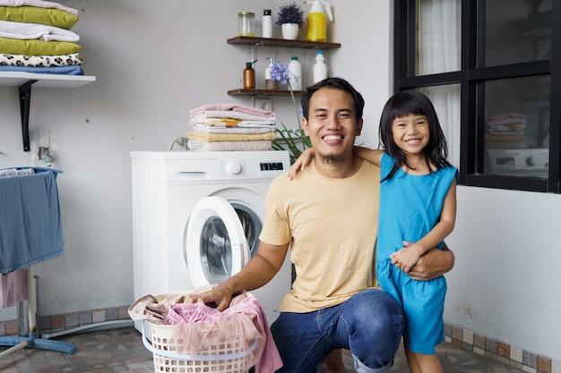 Asiatique famille heureuse homme père ménage et enfant fille dans la lessive avec machine à laver ensemble