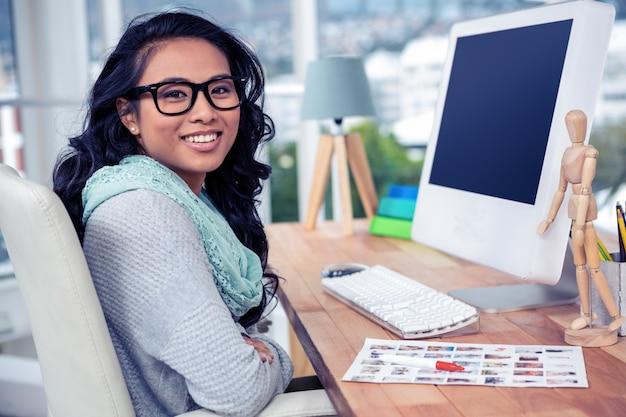 Asiatique femme d'affaires assis dans le bureau et souriant à la caméra