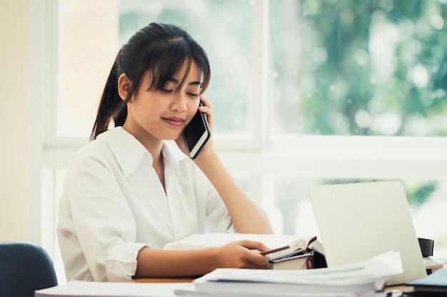 Asiatique, femme affaires, ou, employé bureau, tient, smartphone, parler, sur, appel téléphonique, et, vérification, données