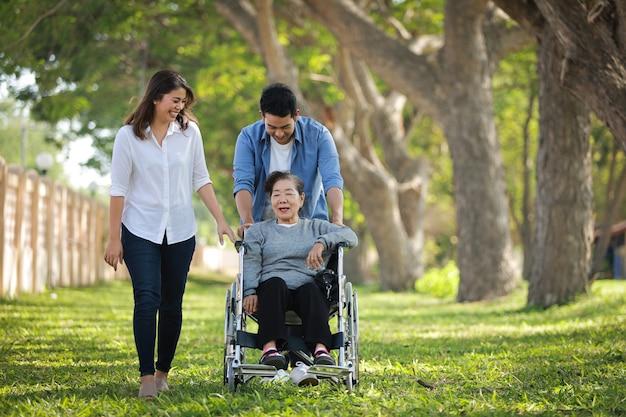 Asiatique femme âgée assise sur le fauteuil roulant avec la famille sourire heureux visage sur le parc verdoyant
