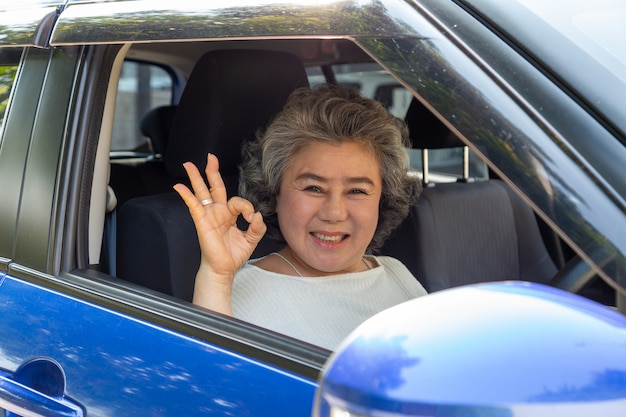 Asiatique femme âgée conduisant une voiture montrant ok avec une expression positive heureuse pendant le trajet pour voyager, les gens aiment rire transport et conduire à travers le concept