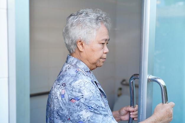Asiatique femme âgée patiente ouverte salle de bain toilette.