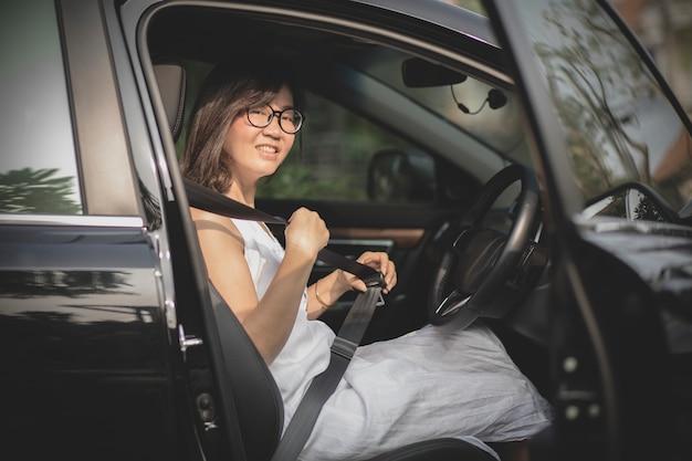 Asiatique femme assise dans le siège du conducteur de la voiture berline attacher la ceinture de sécurité