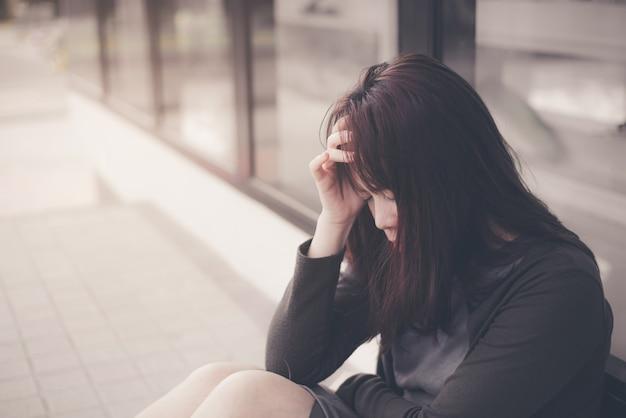 Asiatique femme assise seule et déprimée, portrait de jeune femme fatiguée. dépression