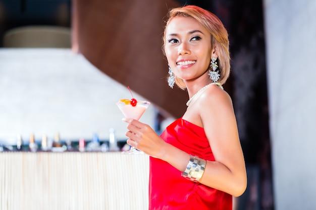 Asiatique femme buvant des cocktails au bar ou au club